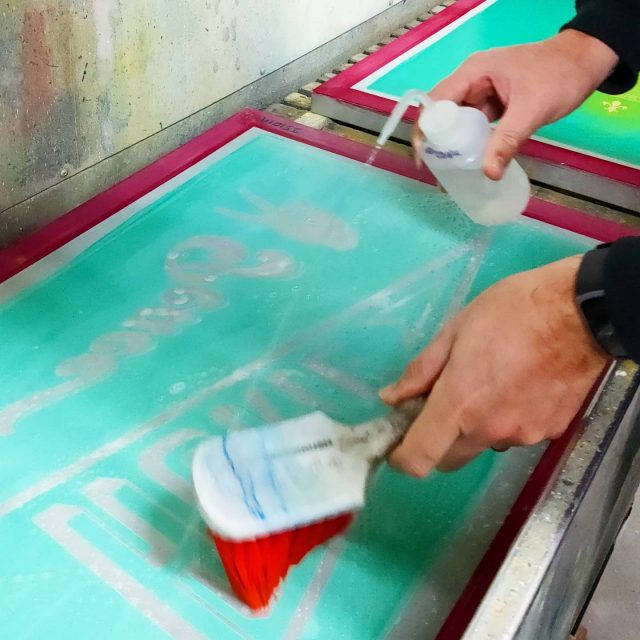 It's time to reclaim some screens so we can make some fresh stuff! Here James is putting down some chemicals that break down the emulsion - the first step in the process 👩🔬. . #screenprintingbrisbane #maintenanceday #silkscreenprinting #parttimescientists😆